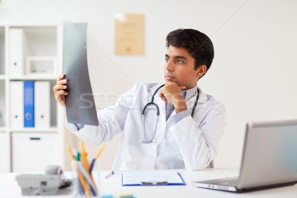doctor looking at spine x-ray scan at clinic Stock photo © dolgachov