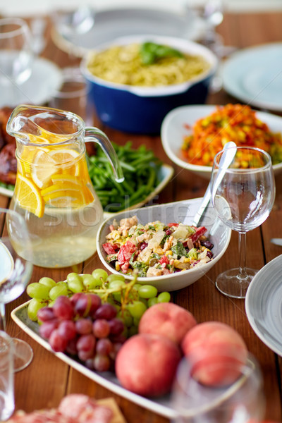 salad, jug of water and other food on wooden table Stock photo © dolgachov