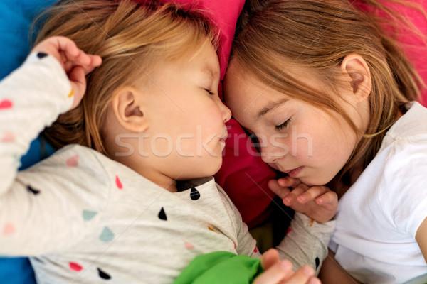 Boldog kislányok alszik ágy otthon gyermekkor Stock fotó © dolgachov