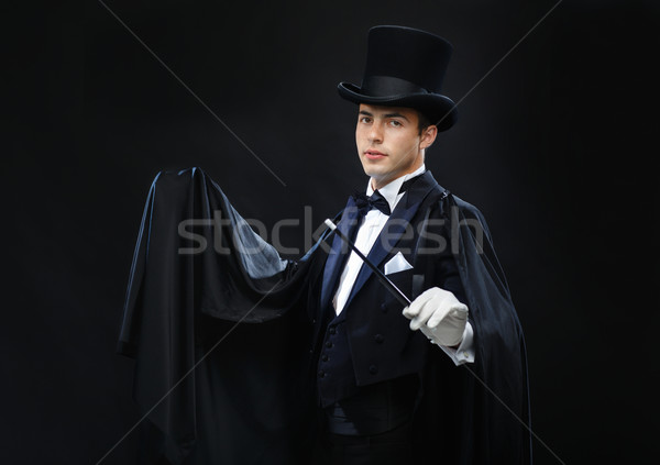 magician in top hat with magic wand showing trick Stock photo © dolgachov