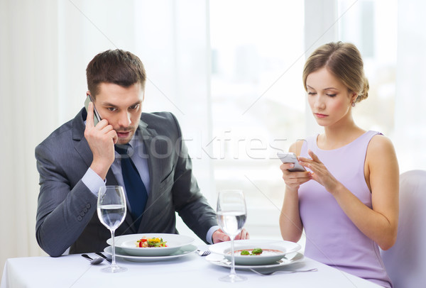 busy couple with smartphones at restaurant Stock photo © dolgachov