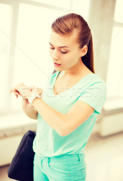 surprised student girl looking at wristwatch Stock photo © dolgachov