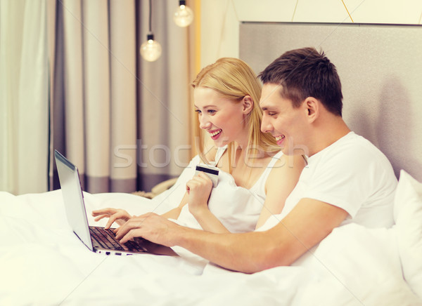 couple in bed with laptop computer and credit card Stock photo © dolgachov