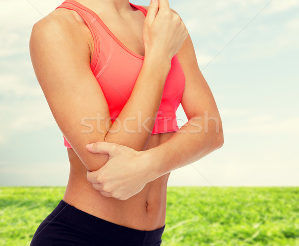 sporty woman with pain in elbow Stock photo © dolgachov