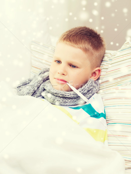 ill boy with thermometer lying in bed at home Stock photo © dolgachov