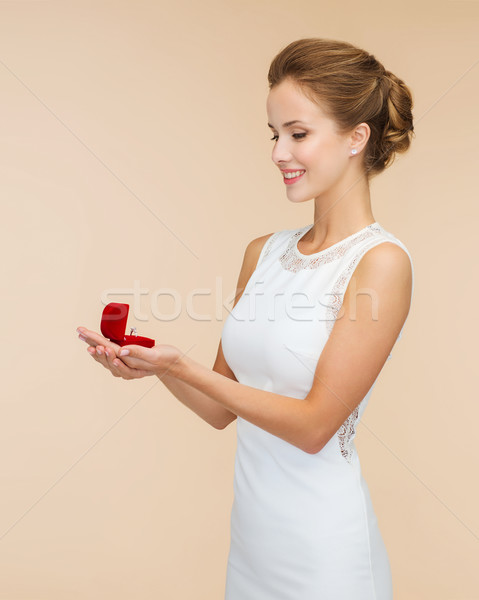 smiling woman holding red gift box with ring Stock photo © dolgachov