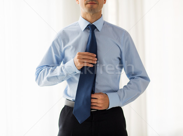 close up of man in shirt adjusting tie on neck Stock photo © dolgachov