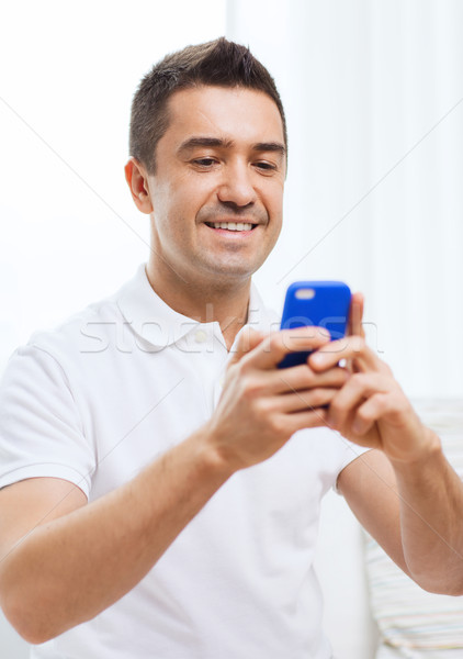 happy man with smartphone at home Stock photo © dolgachov