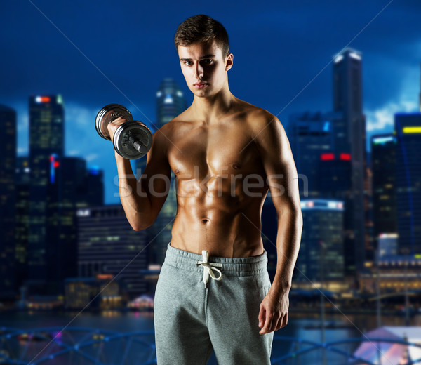 Fiatalember súlyzó bicepsz sport fitnessz súlyemelés Stock fotó © dolgachov