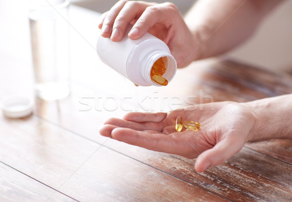 Stock photo: close up of man pouring fish oil capsules to hand