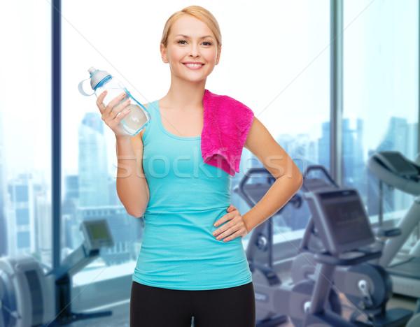 Gelukkig vrouw fles water handdoek gymnasium Stockfoto © dolgachov