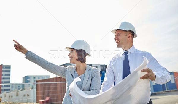 happy architects with blueprint at building Stock photo © dolgachov