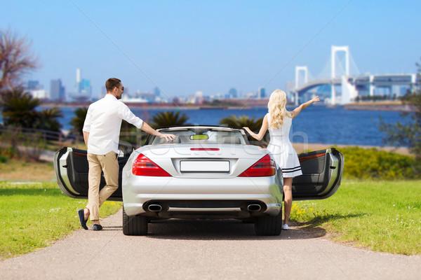 happy man and woman near cabriolet car in tokyo Stock photo © dolgachov