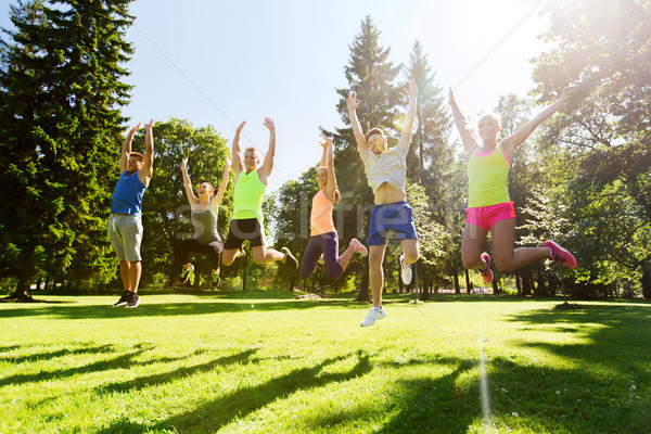 group of happy friends jumping high outdoors Stock photo © dolgachov