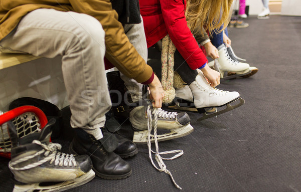 Stock photo: close up of friends wearing skates on skating rink