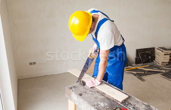close up of builder with arm saw sawing board Stock photo © dolgachov