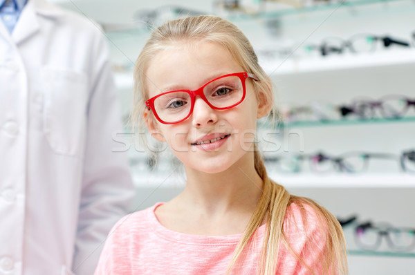 girl in glasses with optician at optics store Stock photo © dolgachov