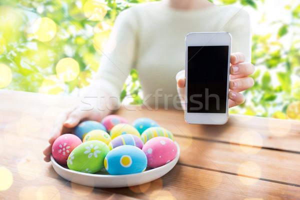 close up of woman with easter eggs and smartphone Stock photo © dolgachov