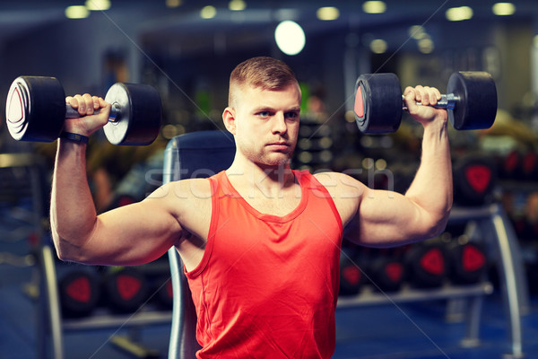 young man with dumbbells flexing muscles in gym Stock photo © dolgachov
