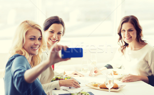 Stock photo: women with smartphone taking selfie at restaurant