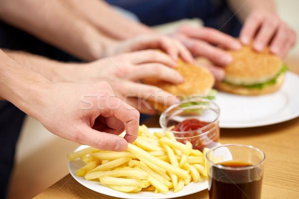 Mannelijke handen fast food tabel ongezond eten Stockfoto © dolgachov