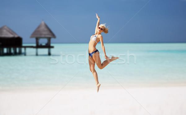 Felice jumping esotiche spiaggia persone Foto d'archivio © dolgachov