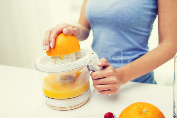 close up of woman squeezing orange juice at home Stock photo © dolgachov