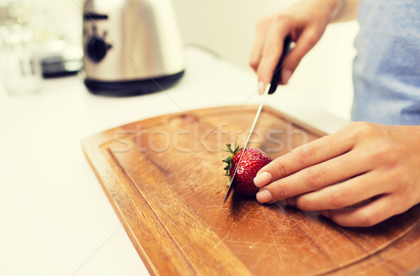 close up of woman chopping strawberry at home Stock photo © dolgachov
