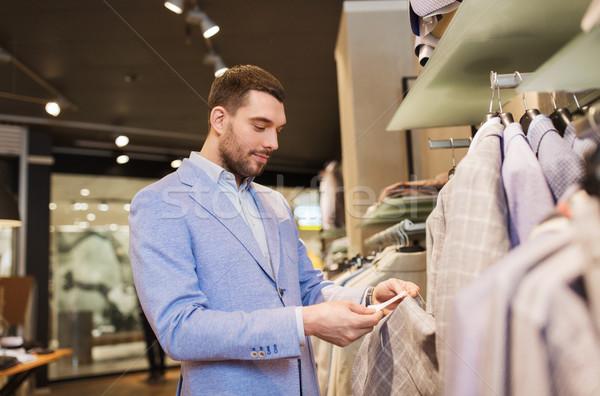 Boldog fiatalember választ ruházat ruházat bolt Stock fotó © dolgachov