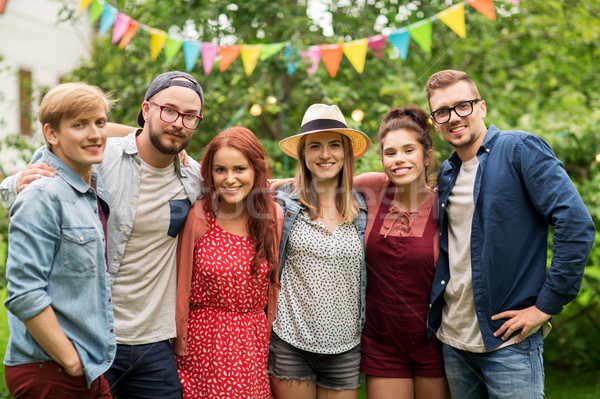 Stock photo: happy teenage friends hugging at summer garden