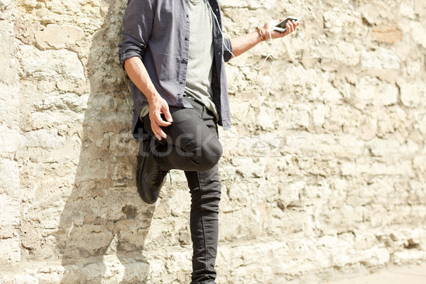 man with earphones and smartphone on street Stock photo © dolgachov