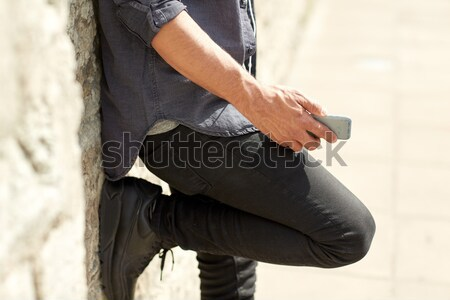 close up of man with smartphone at stone wall Stock photo © dolgachov