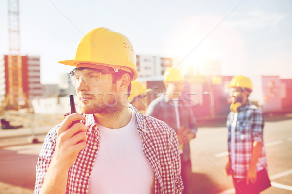group of builders in hardhats with radio Stock photo © dolgachov