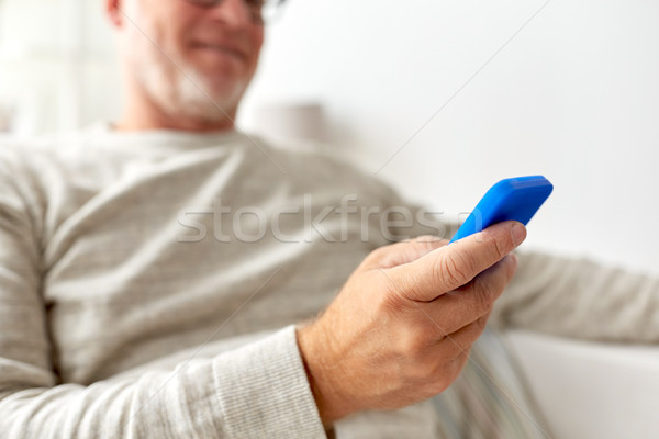close up of old man texting on smartphone at home Stock photo © dolgachov