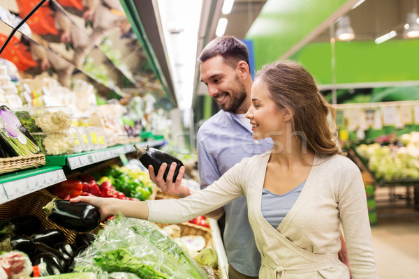 happy couple buying eggplant at grocery store Stock photo © dolgachov
