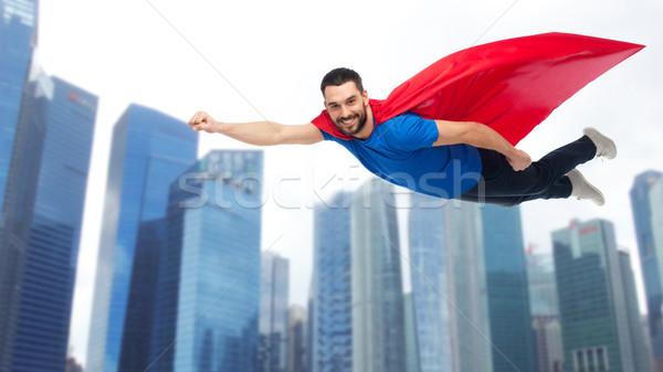 happy man in red superhero cape flying over city Stock photo © dolgachov