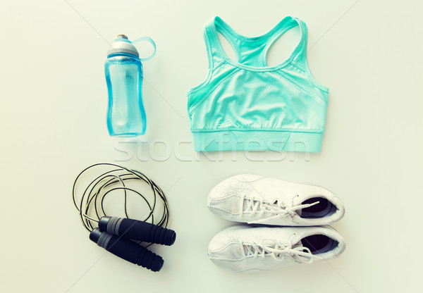 close up of sportswear, skipping rope and bottle Stock photo © dolgachov