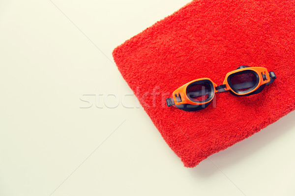close up of swimming goggles and towel Stock photo © dolgachov
