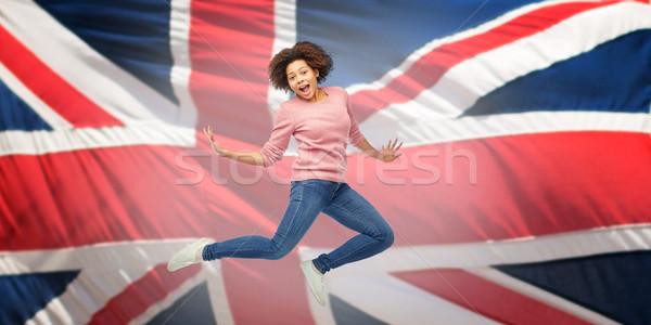 Afroamerikai nő ugrik angol zászló emberek mozgás Stock fotó © dolgachov