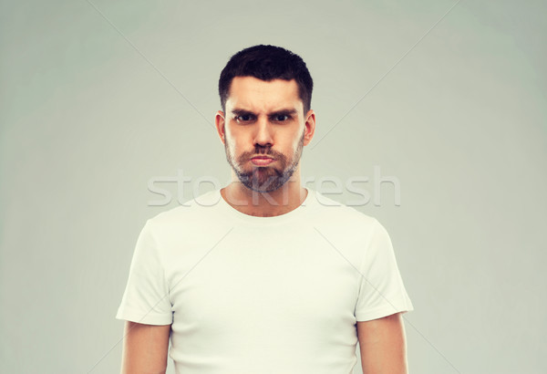 man with funny angry face over gray background Stock photo © dolgachov