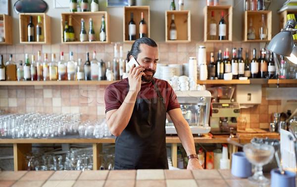 happy man or waiter at bar calling on smartphone Stock photo © dolgachov