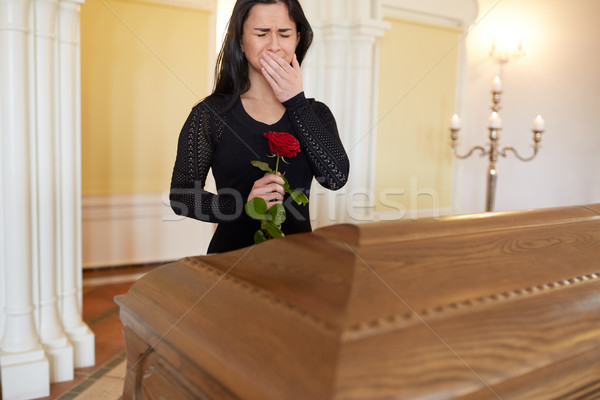 crying woman with red rose and coffin at funeral Stock photo © dolgachov