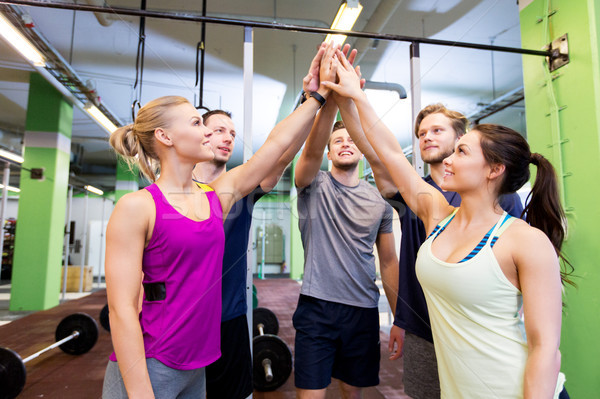 group of happy friends making high five in gym Stock photo © dolgachov