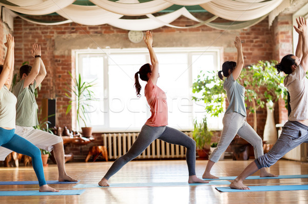 group of people doing yoga warrior pose at studio Stock photo © dolgachov