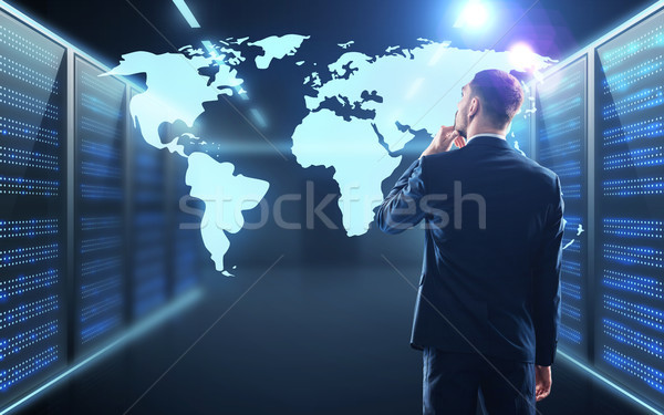 businessman with world map projection in corridor Stock photo © dolgachov
