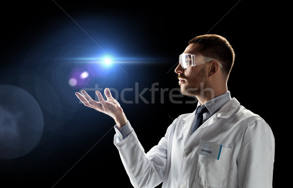 scientist in lab coat and goggles with laser light Stock photo © dolgachov