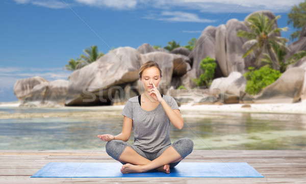 woman doing yoga breathing exercise on beach Stock photo © dolgachov