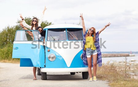 Stock photo: happy hippie friends in minivan car on beach