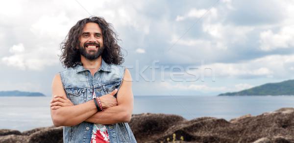 Sorridente hippie homem brim colete ilha Foto stock © dolgachov