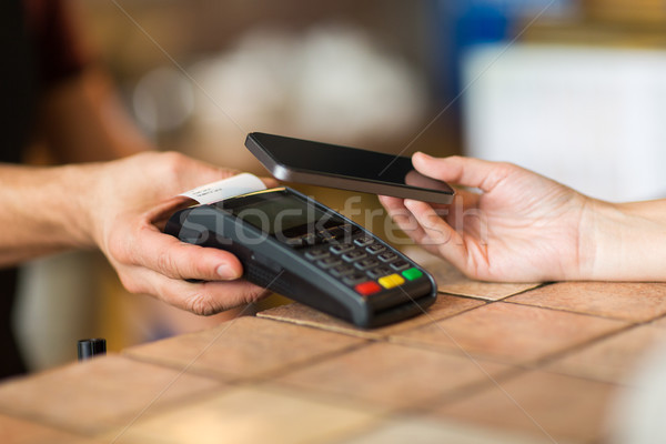 hands with payment terminal and smartphone at bar Stock photo © dolgachov